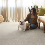 Woman with pet on Carpet | Hughes Floor Coverings Inc.