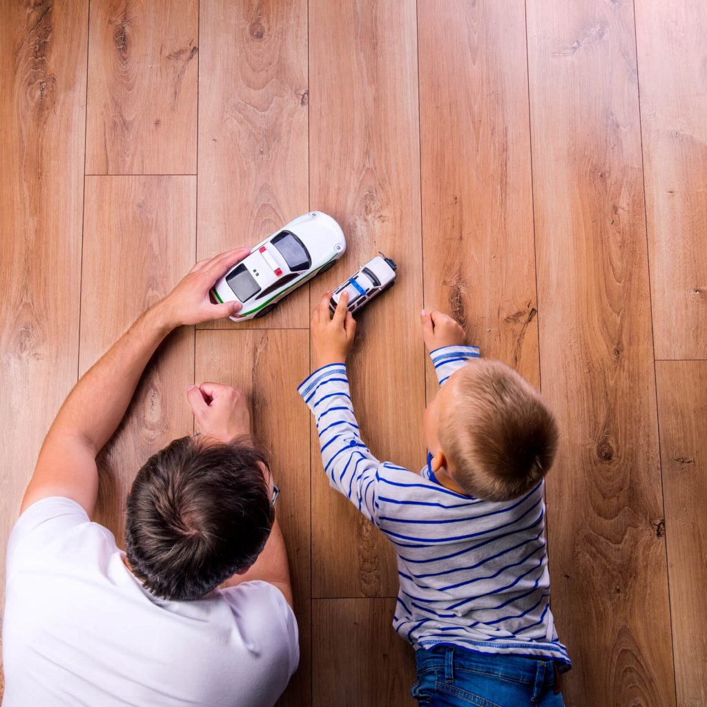 Kid and father playing on Hardwood floor | Hughes Floor Coverings Inc
